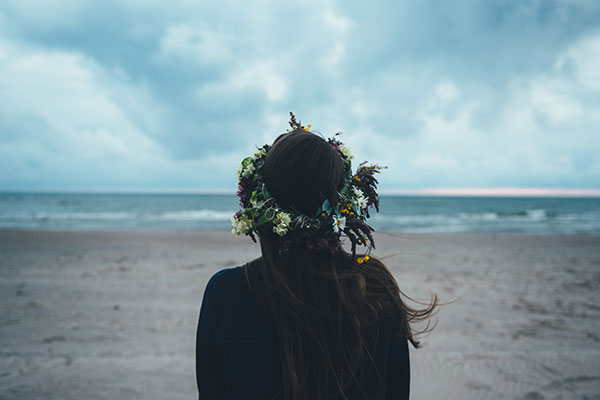 woman with long hair looking at the sea