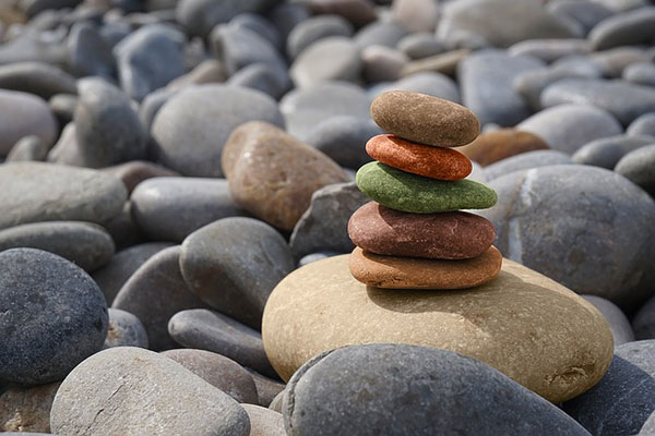 coloured rocks balanced on larger ones on beach