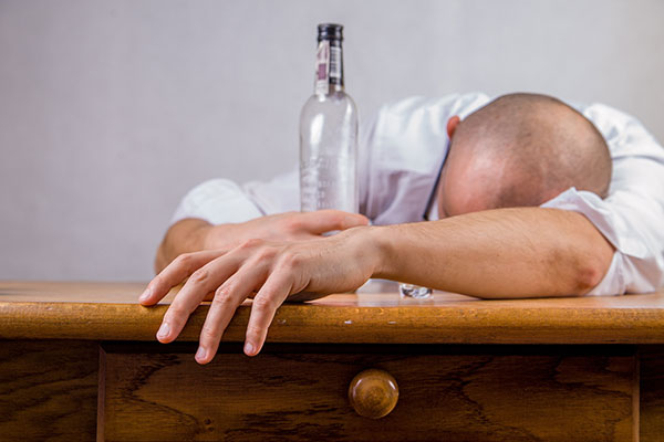 man laying face down on desk with an empty bottle image represents unconscious through drink