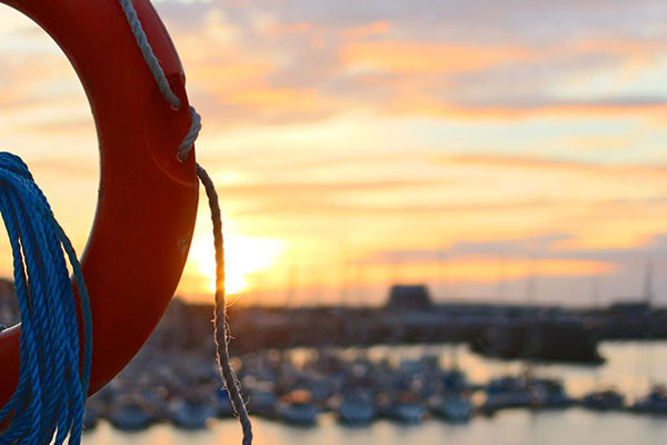 sunset over harbour with lots of small fishing boats