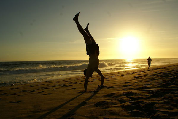 Man doing a handstand on a beach