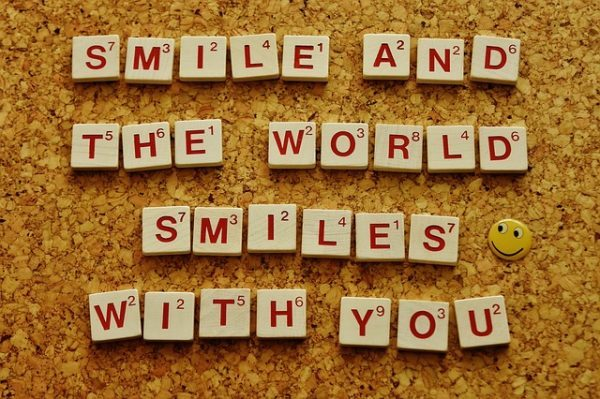 scrabble tiles spelling smile and the world smiles with you