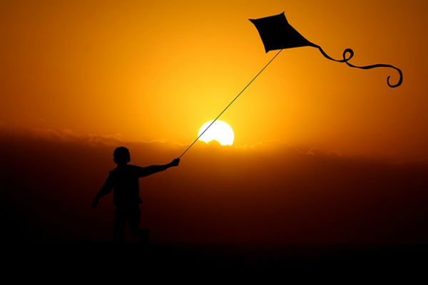 boy flying a kite while the sun sets