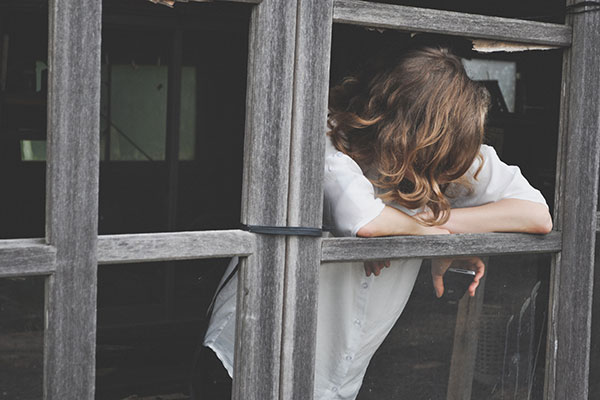 woman leaning out of window. Face obscured, long hair
