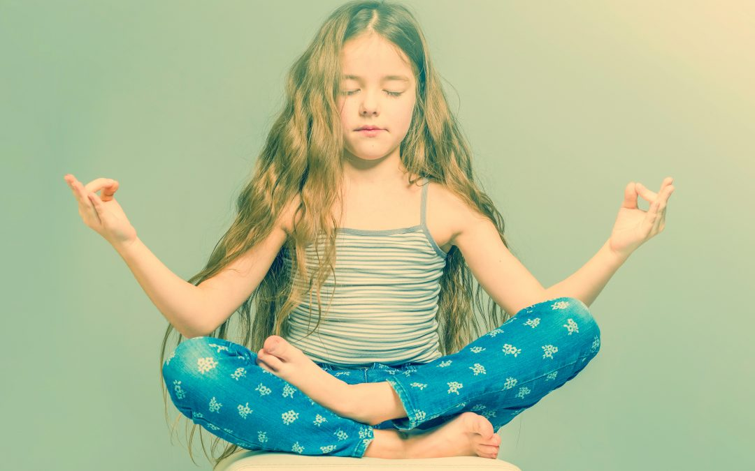 Girl with long hair and in jeans meditating in a lotus pose.