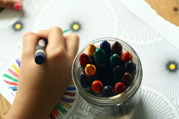 pot of crayons and child colouring
