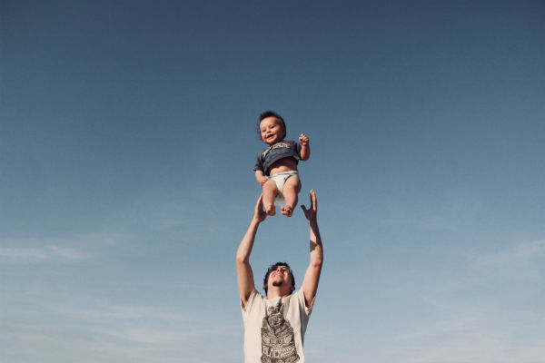 man throwing child in the air