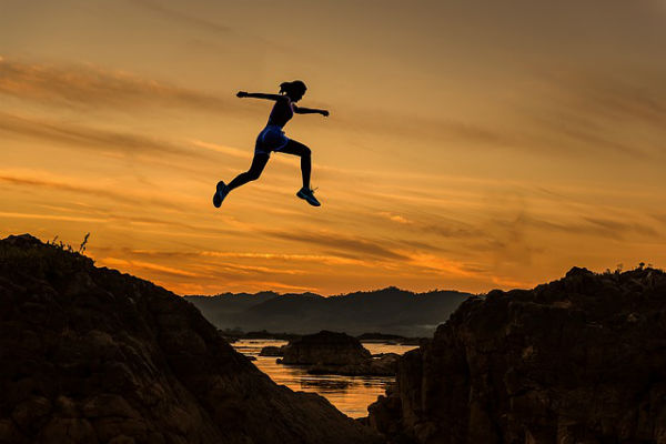 woman jumping during a sunset