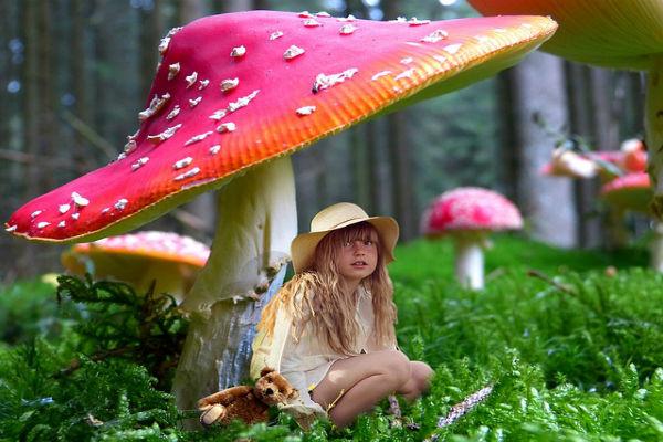 girl sitting under giant mushroom
