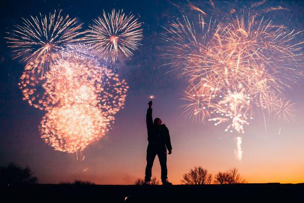 boy holding sparkler as fireworks go off
