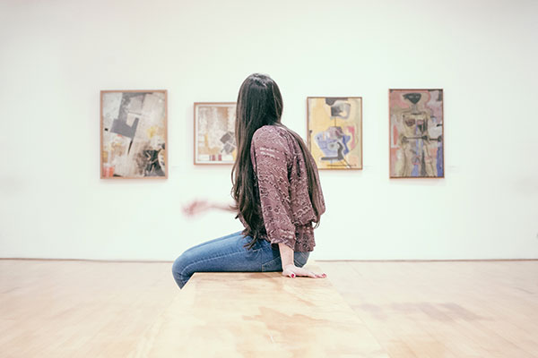 woman sitting in art gallery looking at pictures - rear view
