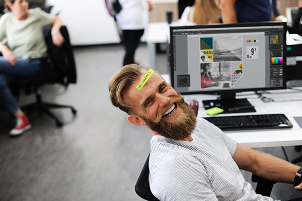 Man with beard and happy label on head for article about improv and humor for The Positive Psychology People website