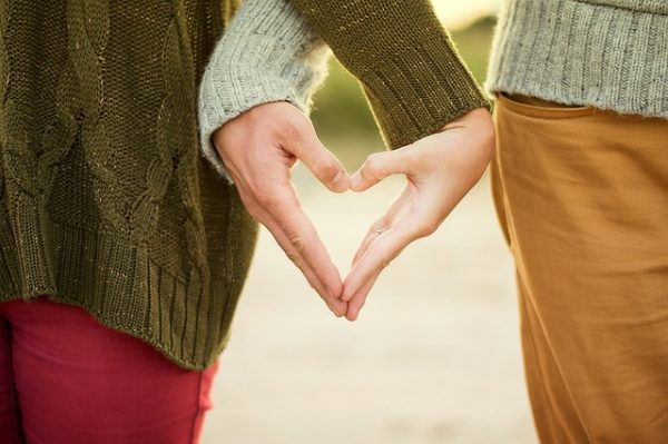 image of man and woman creating a heart shape with their hands - blog about love for the positive psychology people