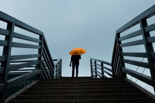 person standing top of stairs with orange umbrella the positive psychology people blog mental health